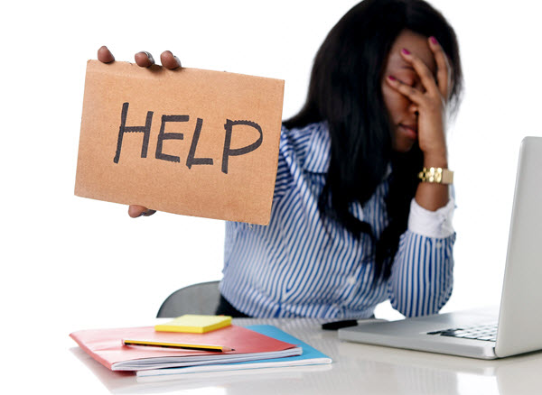 woman-holding-help-sign-in-front-of-laptop-image-from-shutterstock