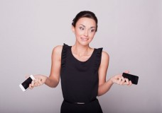 woman-holding-two-cellphones-shrugging-image-from-shutterstock
