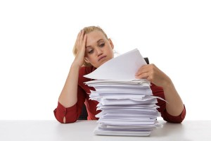 woman-looking-at-stack-of-paper-image-from-shutterstock